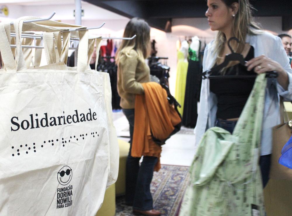 """Descrição da imagem: foto de duas mulheres segurando peças de roupa do Dona Dorina Outlet. À frente delas, no lado esquerdo da imagem, há uma ecobeg da Fundação Dorina com a palavra """"Solidariedade"""""""