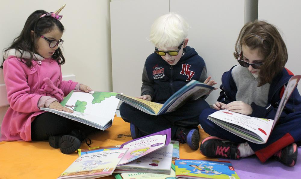 Descrição da imagem: foto de três crianças lendo livros. Todas estão sentadas no chão e usam óculos.