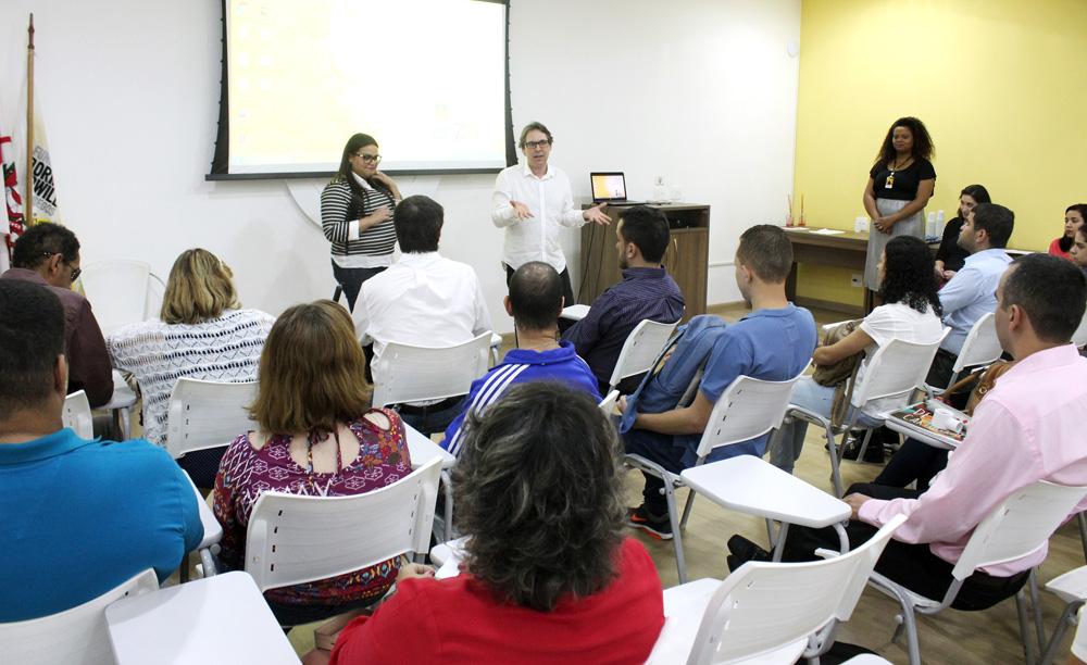 Descrição da imagem: foto de uma sala com dezenas de pessoas sentadas em cadeiras universitárias. À frente delas, de pé, há uma mulher e um homem que gesticula. Atrás deles, um telão em branco.