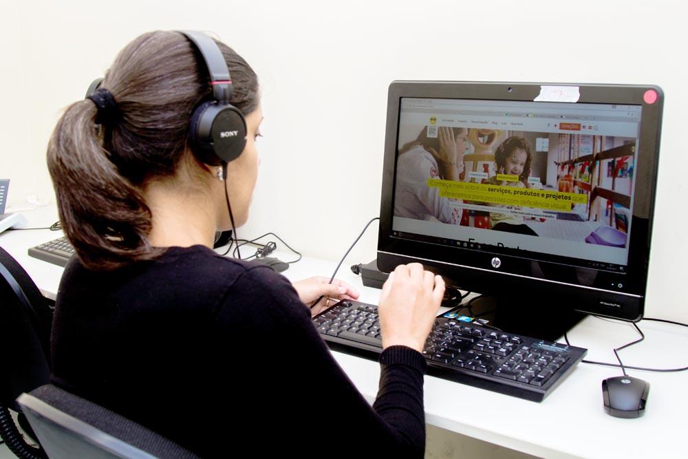 Descrição da imagem: foto de uma moça usando computador. Ela está em meio perfil, usa fones de ouvido e está com as mãos sobre o teclado.