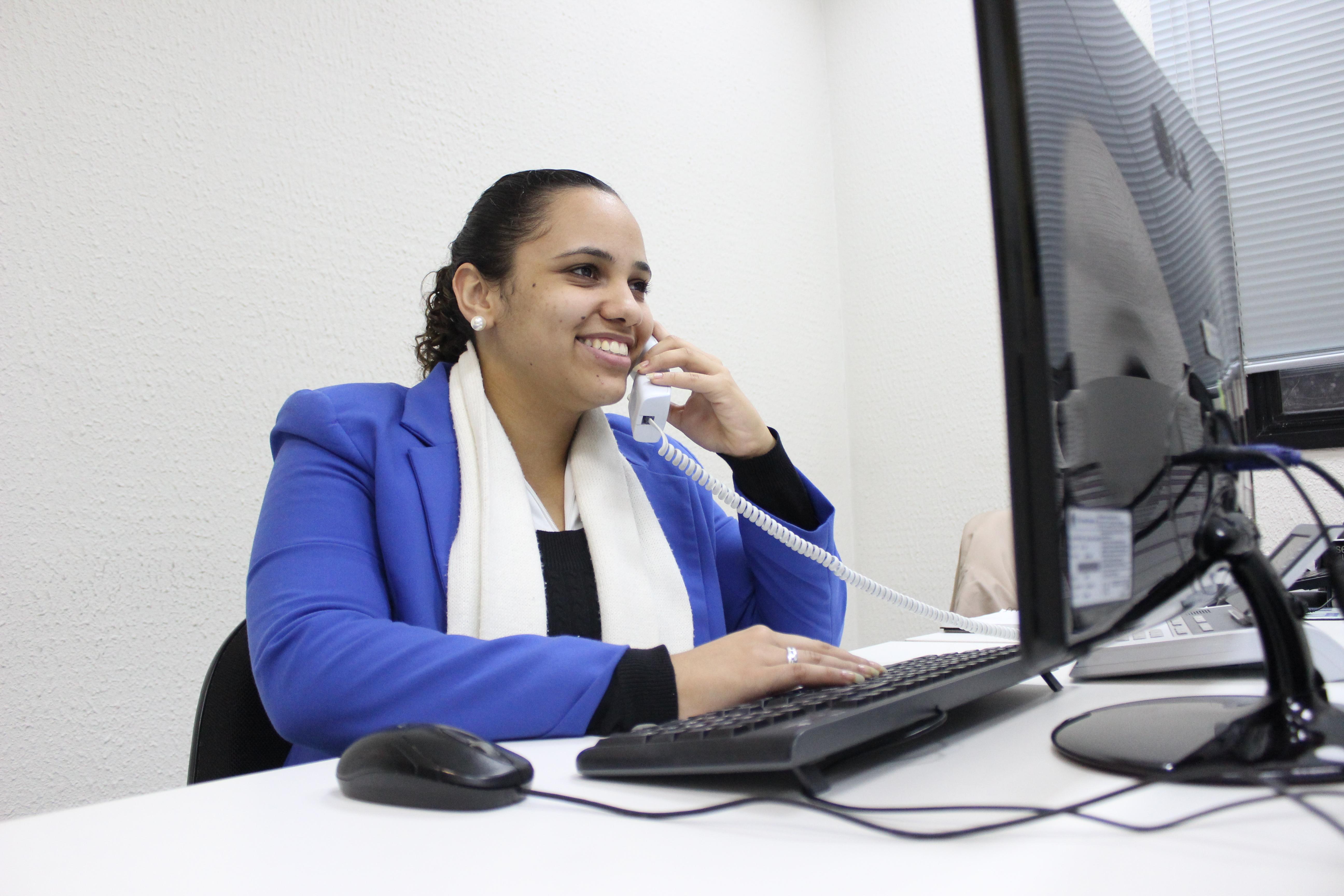 Descrição de imagem: Foto de Stephani Felix utilizando um computador. Ela tem pele clara, cabelos pretos presos em um rabo de cavalo e usa blazer azul com um lenço branco em volta do pescoço. Segura com a mão esquerda um telefone e com a direita digita no teclado.