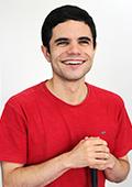Descrição da imagem: foto de Lucas Borba retratado da cintura pra cima. Ele tem pele clara, cabelos pretos e curtos, usa camiseta vermelha, apoia as duas mãos sobre uma bengala e sorri.