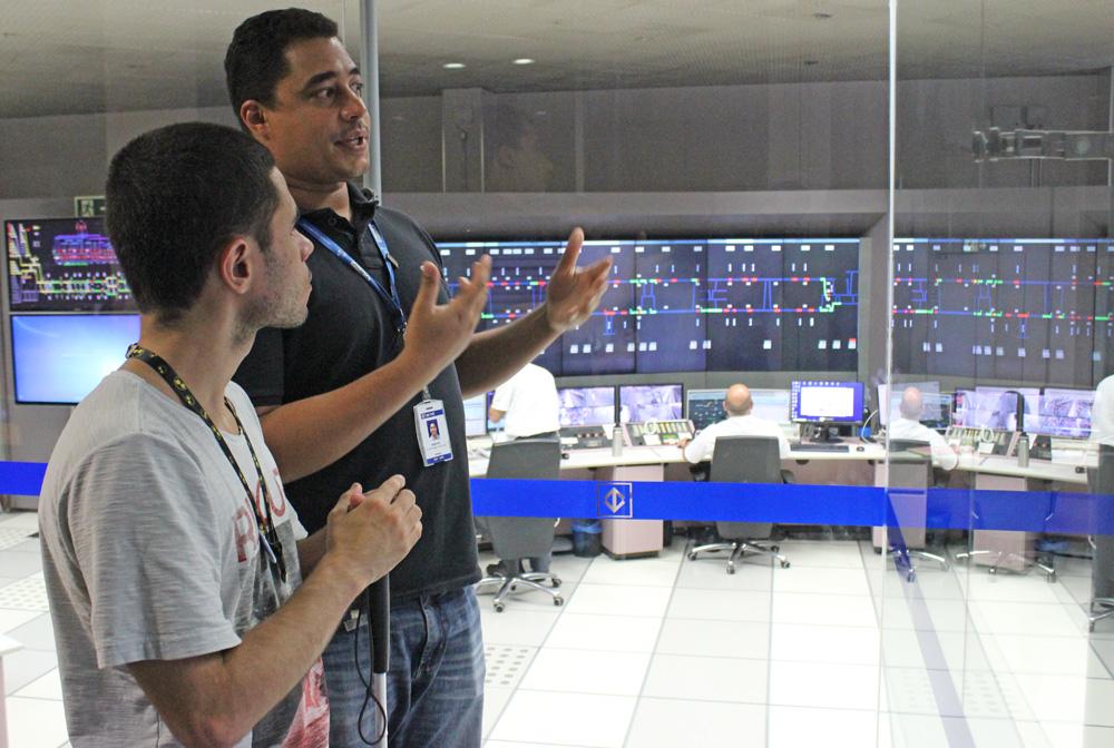 Descrição da imagem: foto de um funcionário do metrô conversando com Lucas no Centro de Controle Operacional. Ao fundo há painéis eletrônicos na parede e pessoas no computador.