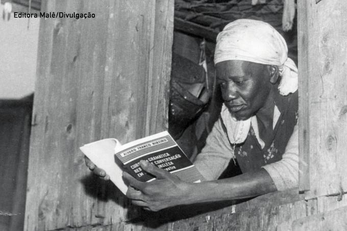 Descrição da imagem: foto em preto e branco de Carolina de Jesus lendo um livro. Ela está debruçada na janela de uma parede de madeira e usa um lenço branco na cabeça.