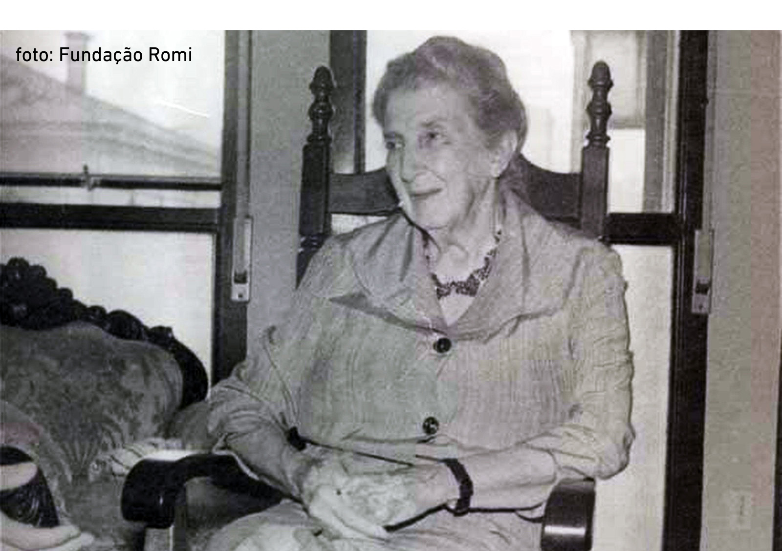 Descrição da imagem: foto em preto e branco de Pérola Byington sentada em uma cadeira de madeira escura. Ela tem cabelos grisalhos, usa casaco de botões, tem as mãos juntas sobre as pernas e sorri.