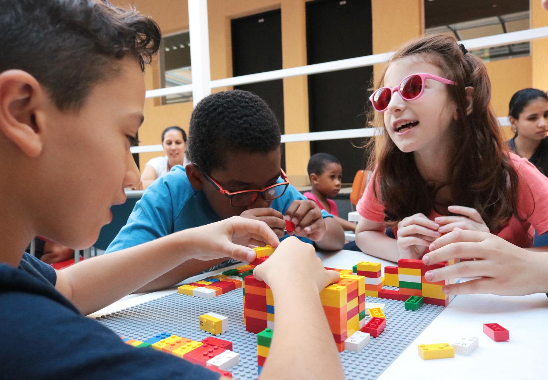 Descrição da imagem: foto de três crianças em volta de uma mesa manuseando peças do LEGO Braille Bricks. Ao fundo há duas mulheres e um menino.