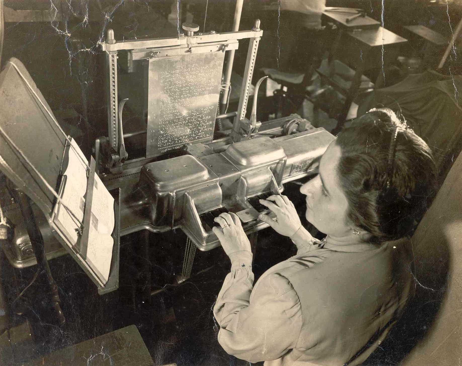 Descrição da imagem: foto em preto e branco de uma mulher com mãos sobre teclas de máquina braille. Ela olha para um livro em tinta posicionado à sua esquerda.