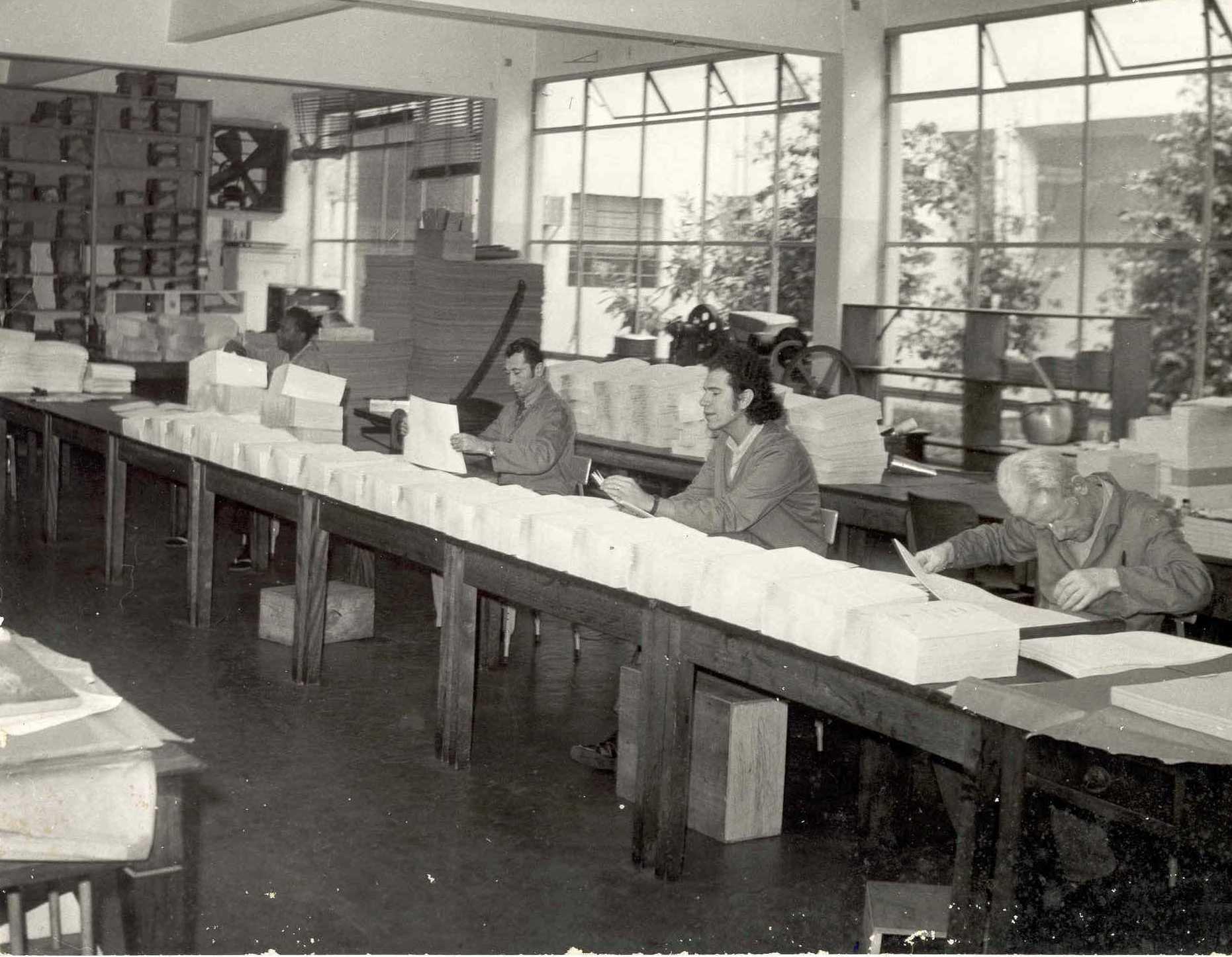 Descrição da imagem: foto em preto e branco de quatro homens manuseando pilhas de papel em branco sobre uma bancada.