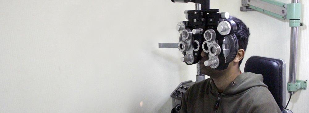 Descrição da imagem: foto de um rapaz sentado com um aparelho oftalmológico à frente do rosto. O aparelho é composto por diversas lentes circulares com pequenas marcações numéricas ao redor.