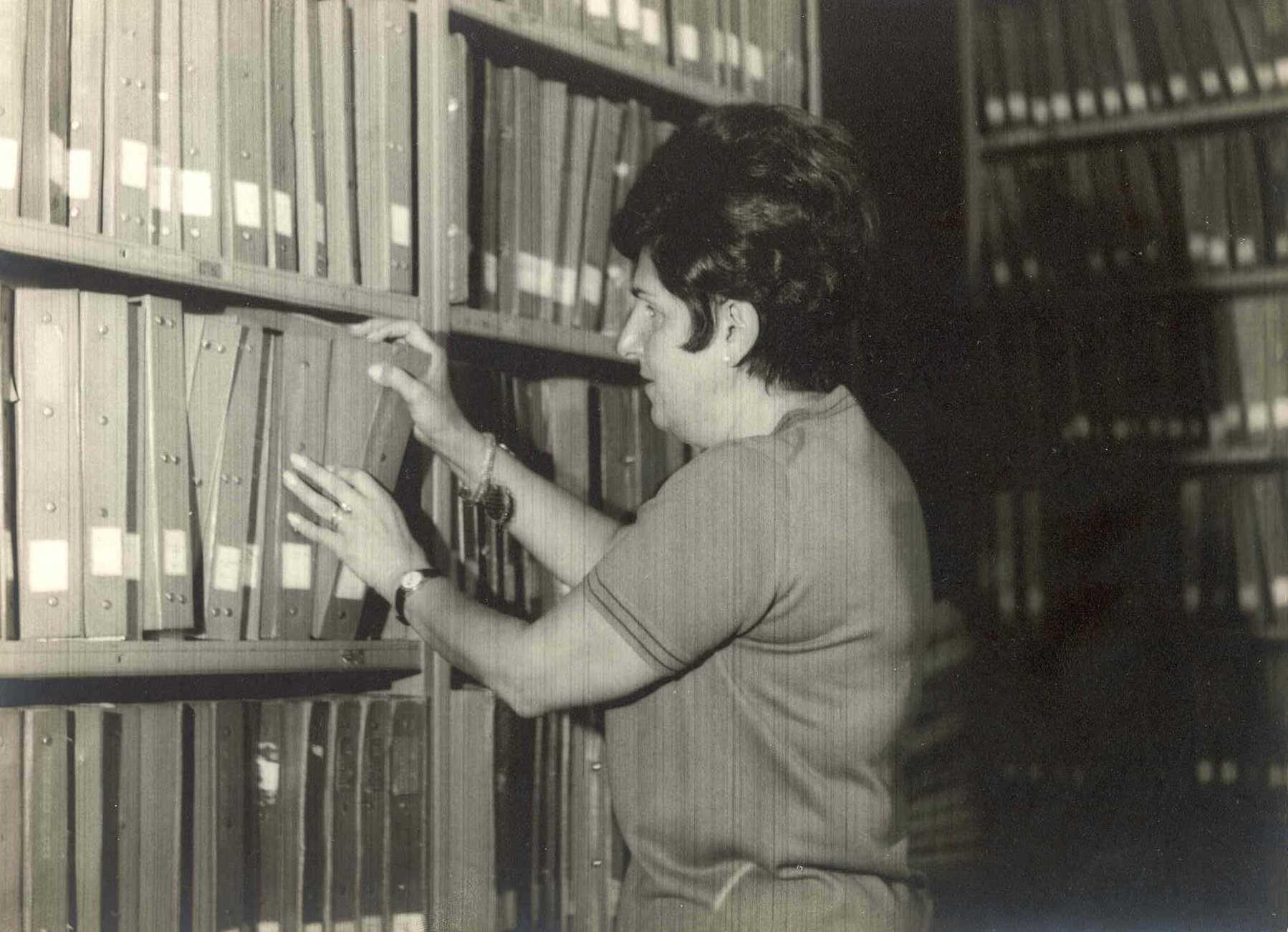 Foto em preto e branco de Dorina escolhendo um livro em uma prateleira cheia.