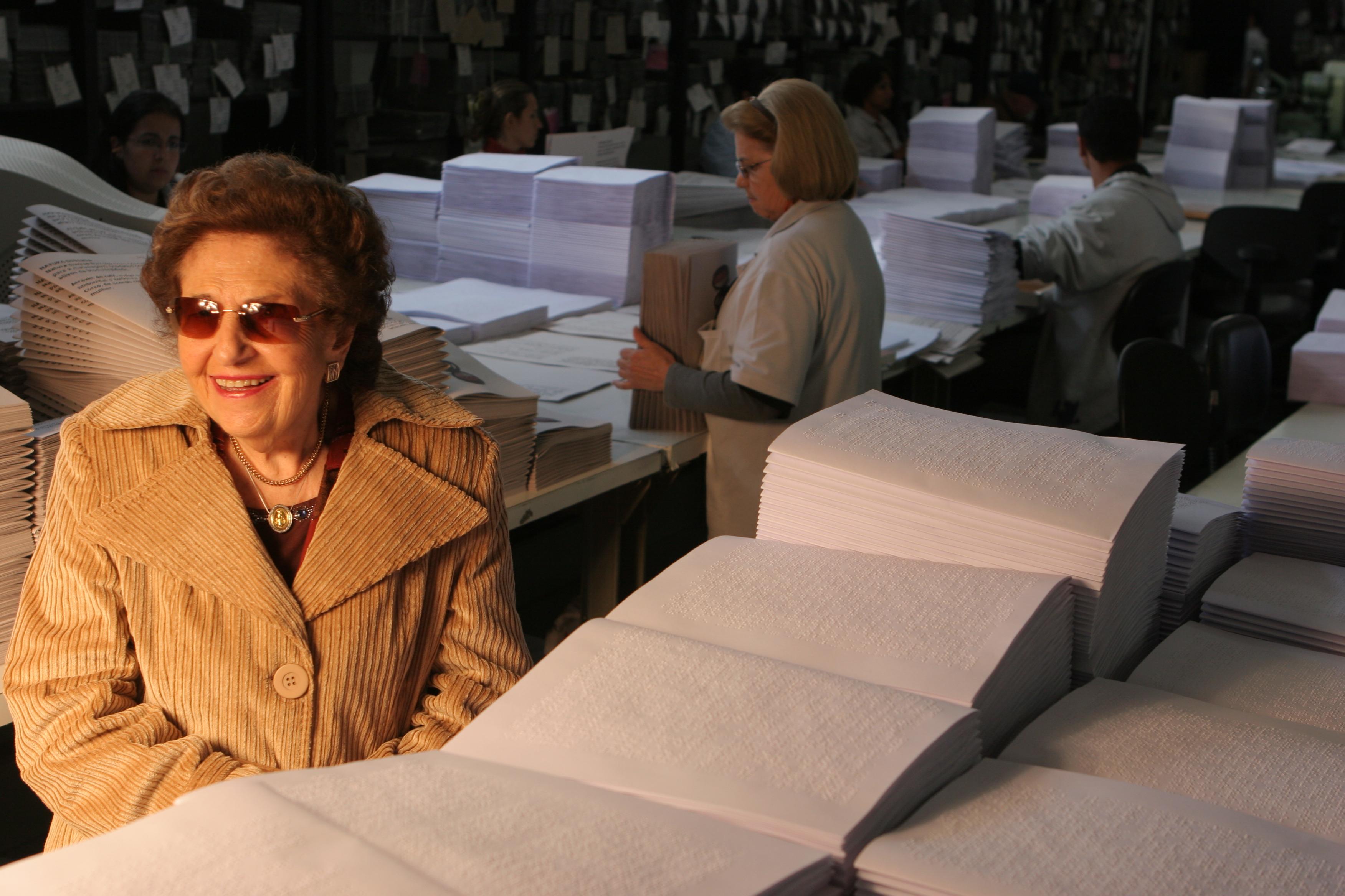 Foto de Dorina sorrindo em frente a vários livros em Braille
