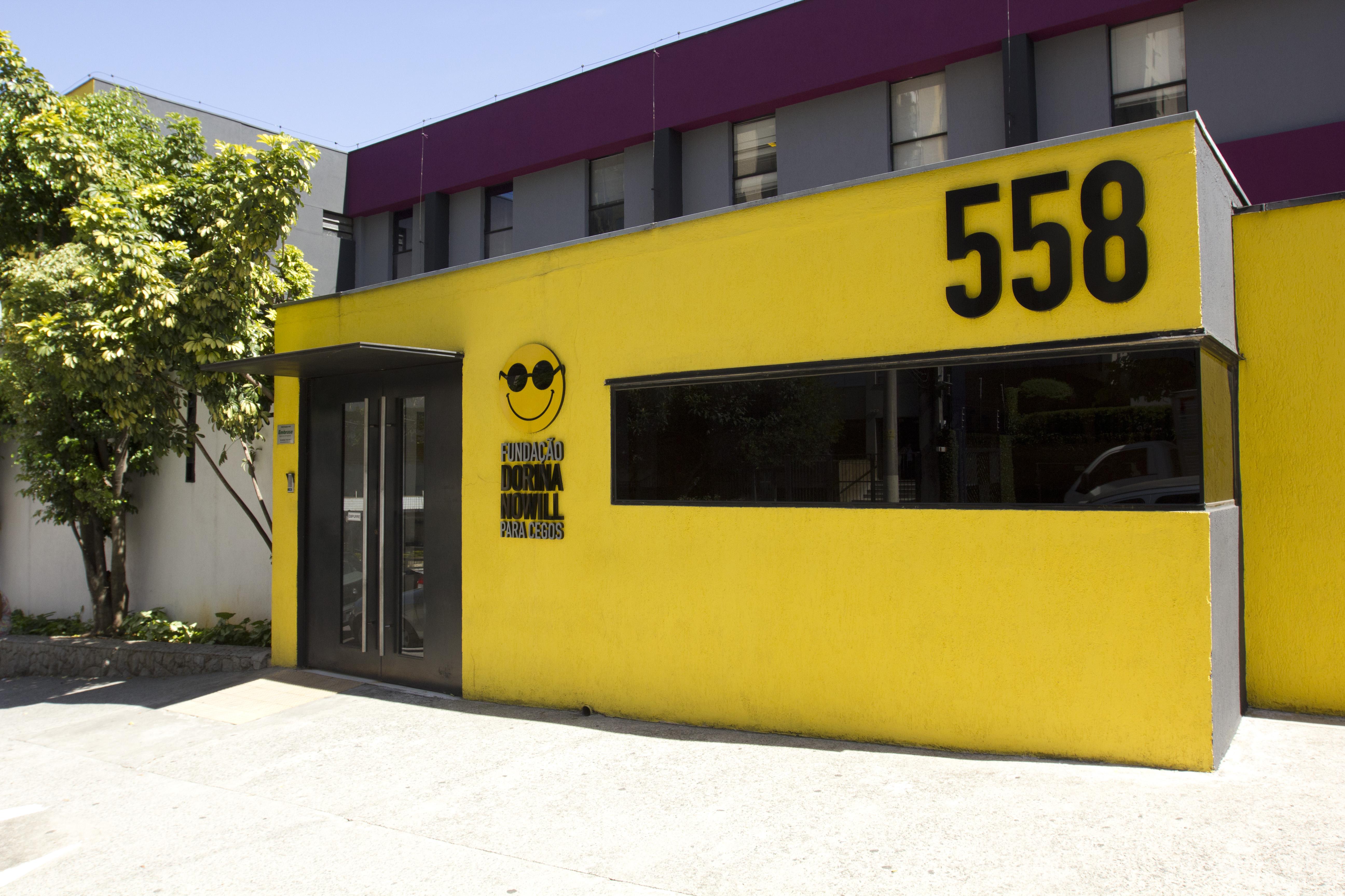 """Foto da fachada da Fundação Dorina. Ela é amarela, possui o logo da Fundação e o número """"558"""" preto."""