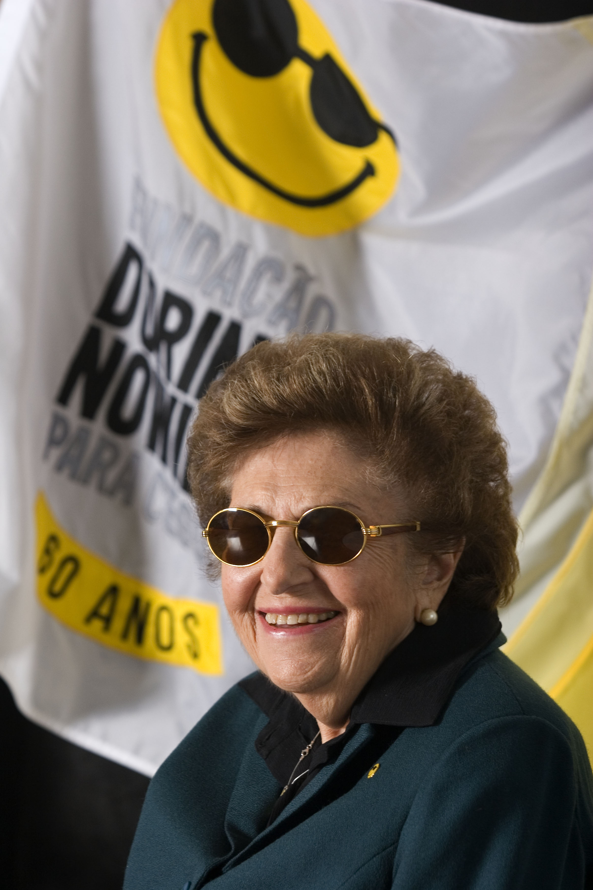 Foto de Dorina com óculos escuros sorrindo. Ao fundo, a bandeira da Fundação.