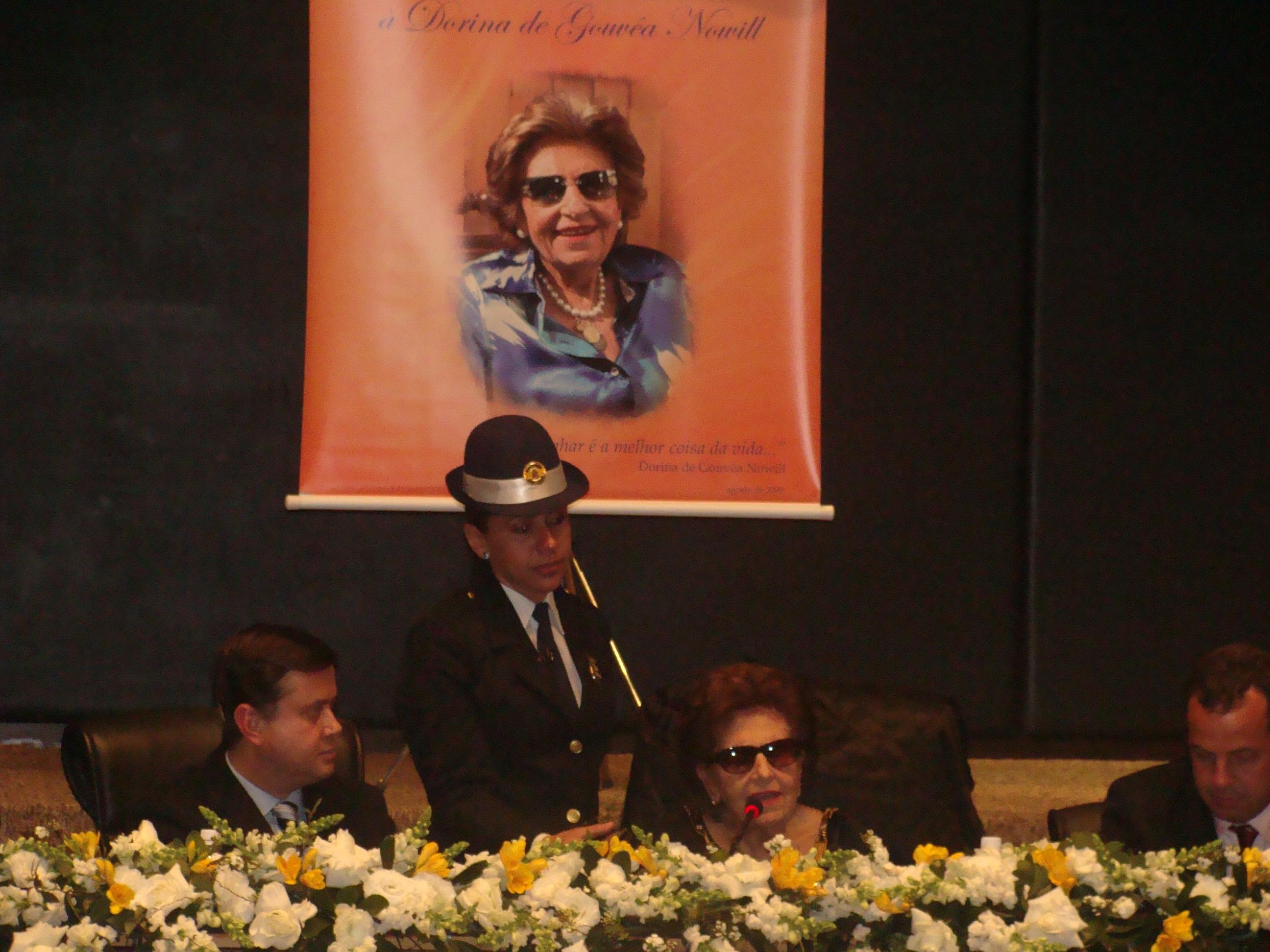 Foto de Dorina sorrindo num palanque com duas pessoas
