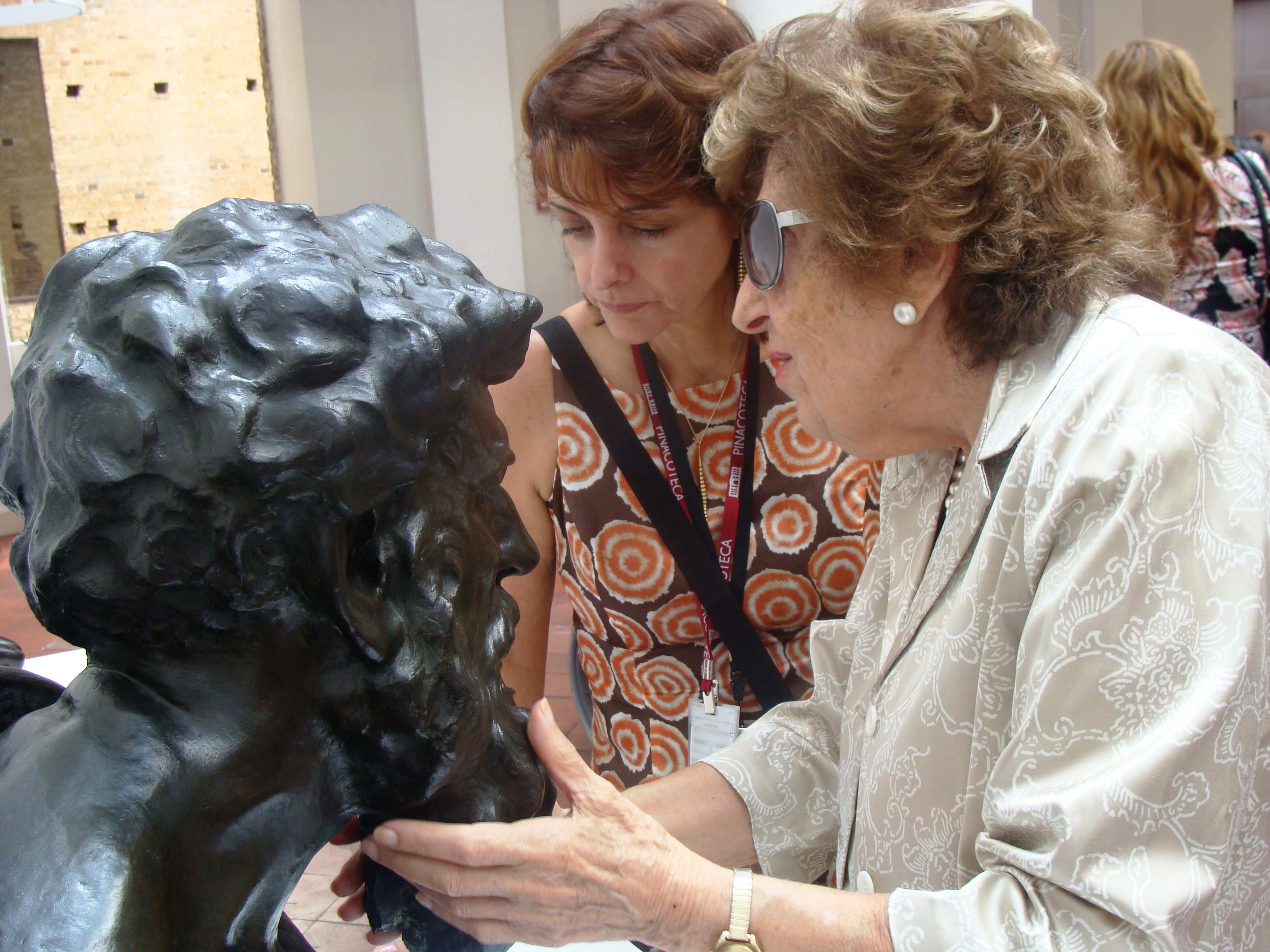 Foto de Dorina tocando a barba de escultura de cabeça masculina em bronze.