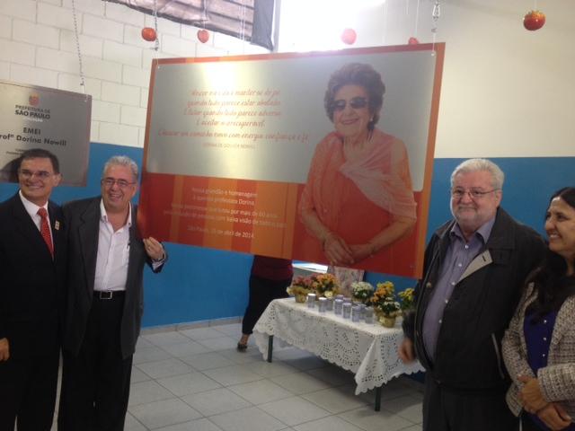 Foto de placa com foto da Dorina e texto ao lado de dois homens que estão dentro da EMEI.