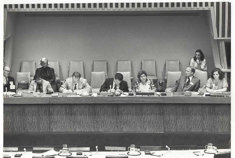 Foto em preto e branco de Dorina sentada em um palanque com outras seis pessoas