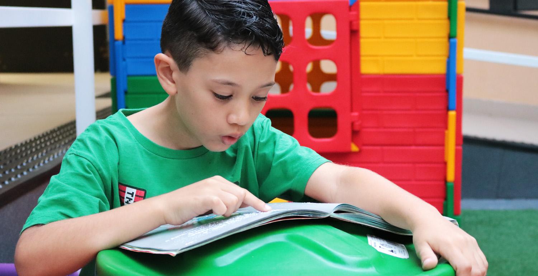 Descrição de imagem: foto de Gustavo lendo um livro aberto à sua frente. Ele tem o dedo indicador apontado para a página.