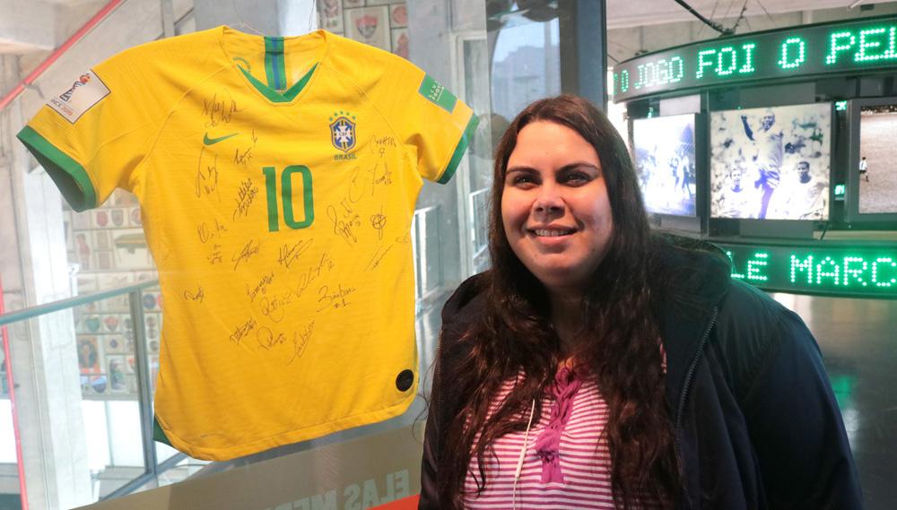 Descrição da imagem: foto de Carla posando ao lado da camisa 10 da jogadora Marta, autografada pelas companheiras de Seleção Brasileira. Carla olha pra frente e sorri.