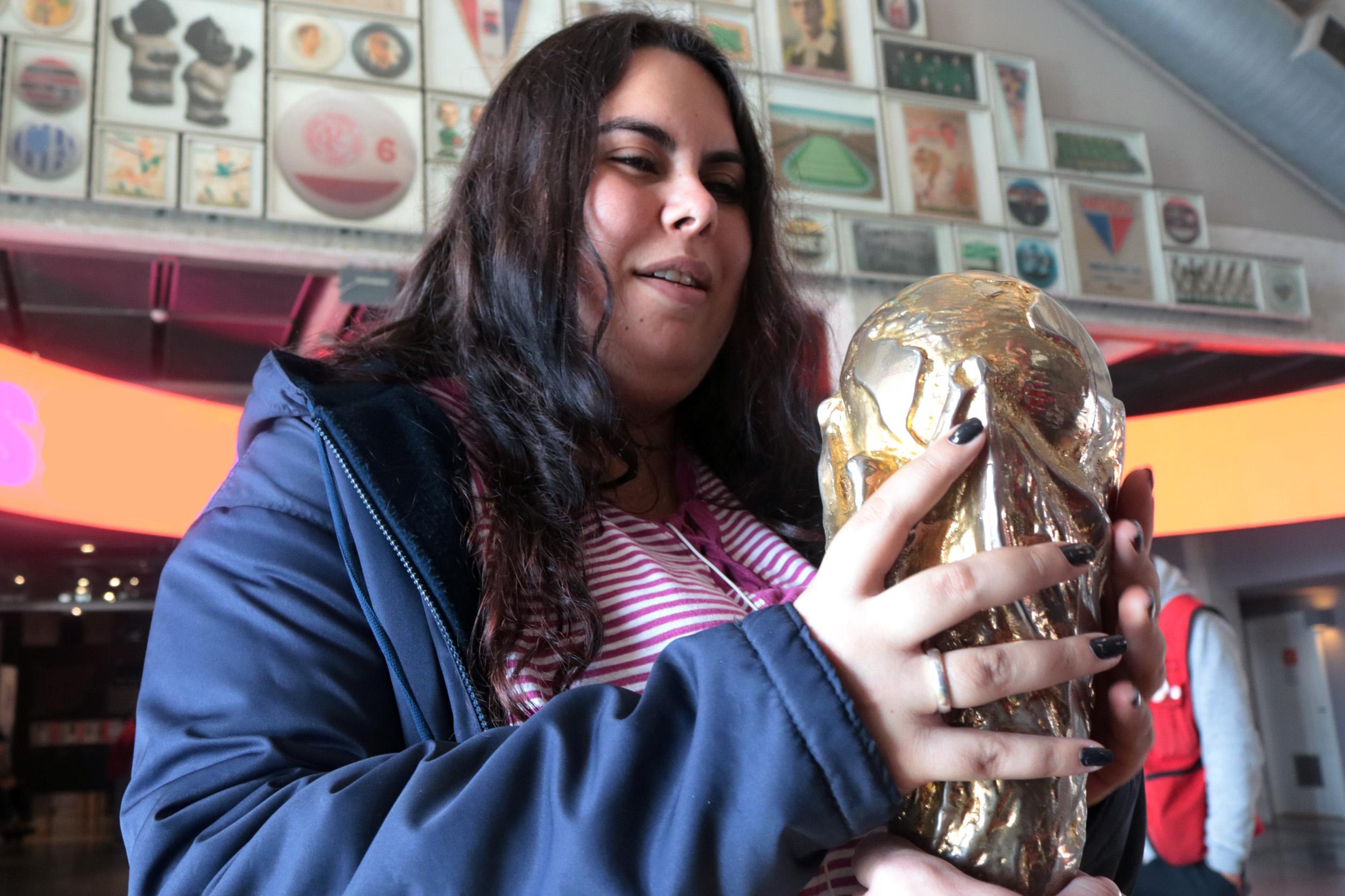 Descrição da imagem: foto de Carla segurando a réplica do troféu da Copa do Mundo. Ao fundo há inúmeros quadros com escudos de times, flâmulas e itens de colecionador relacionados ao futebol.