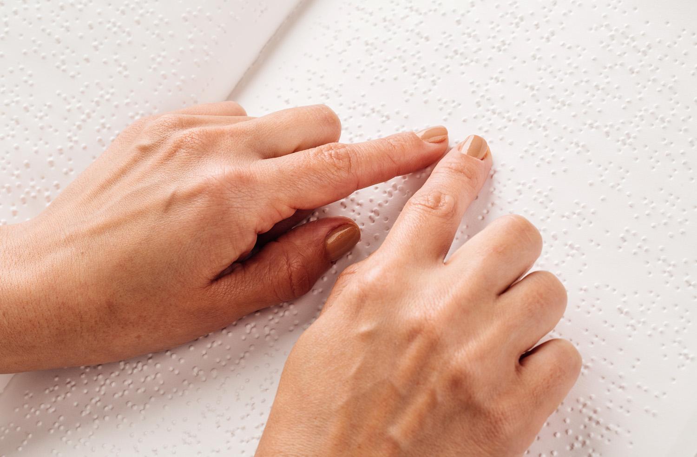 Descrição da imagem: foto de duas mãos com os dedos indicadores tocando uma folha de papel em braille