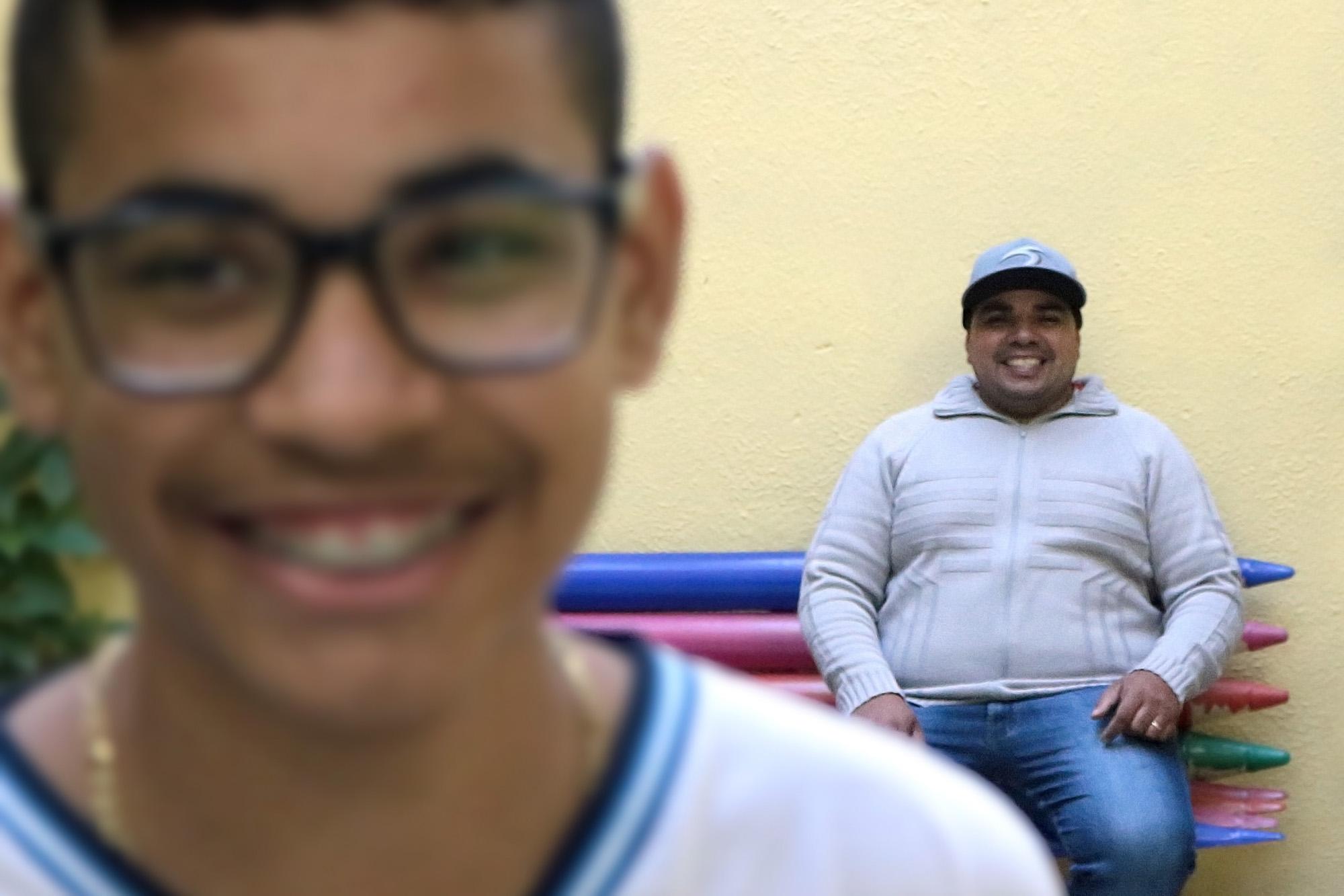 Descrição da imagem: foto de Iago e Moisés sorrindo. Iago está retratado do pescoço pra cima, levemente desfocado. Moisés está cerca de três metros atrás dele, sentado num banco colorido e olhando para o filho. O menino usa óculos e aparelho odontológico..