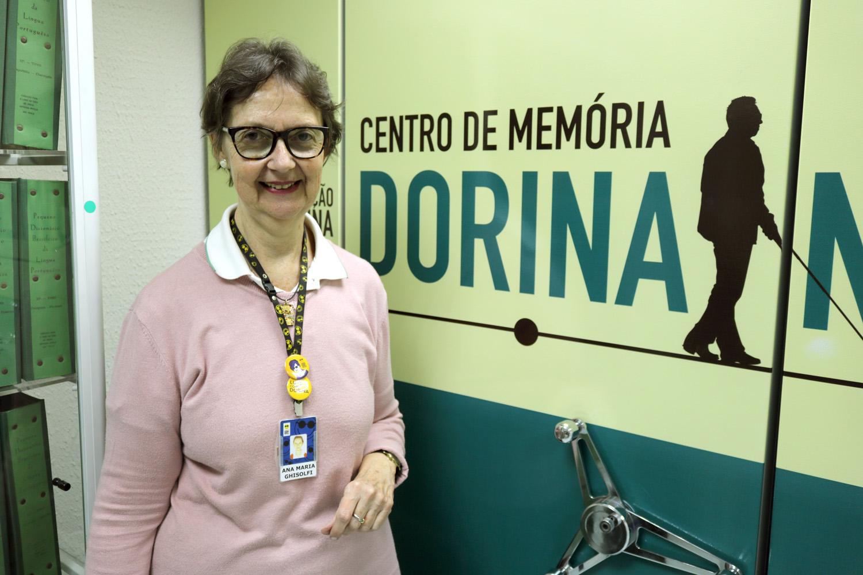 Descrição da imagem: Foto de Ana no Centro de memória da Fundação Dorina. Ela está olhando para foto e sorrindo. Ao fundo: Centro de Memória Dorina.