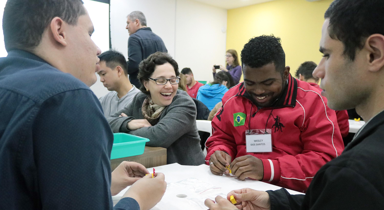 Descrição da imagem: foto de quatro participantes do projeto sentados em roda, manuseando peças de Lego. Dois deles sorriem. Ao fundo há outros grupos em atividade e um homem de pé.