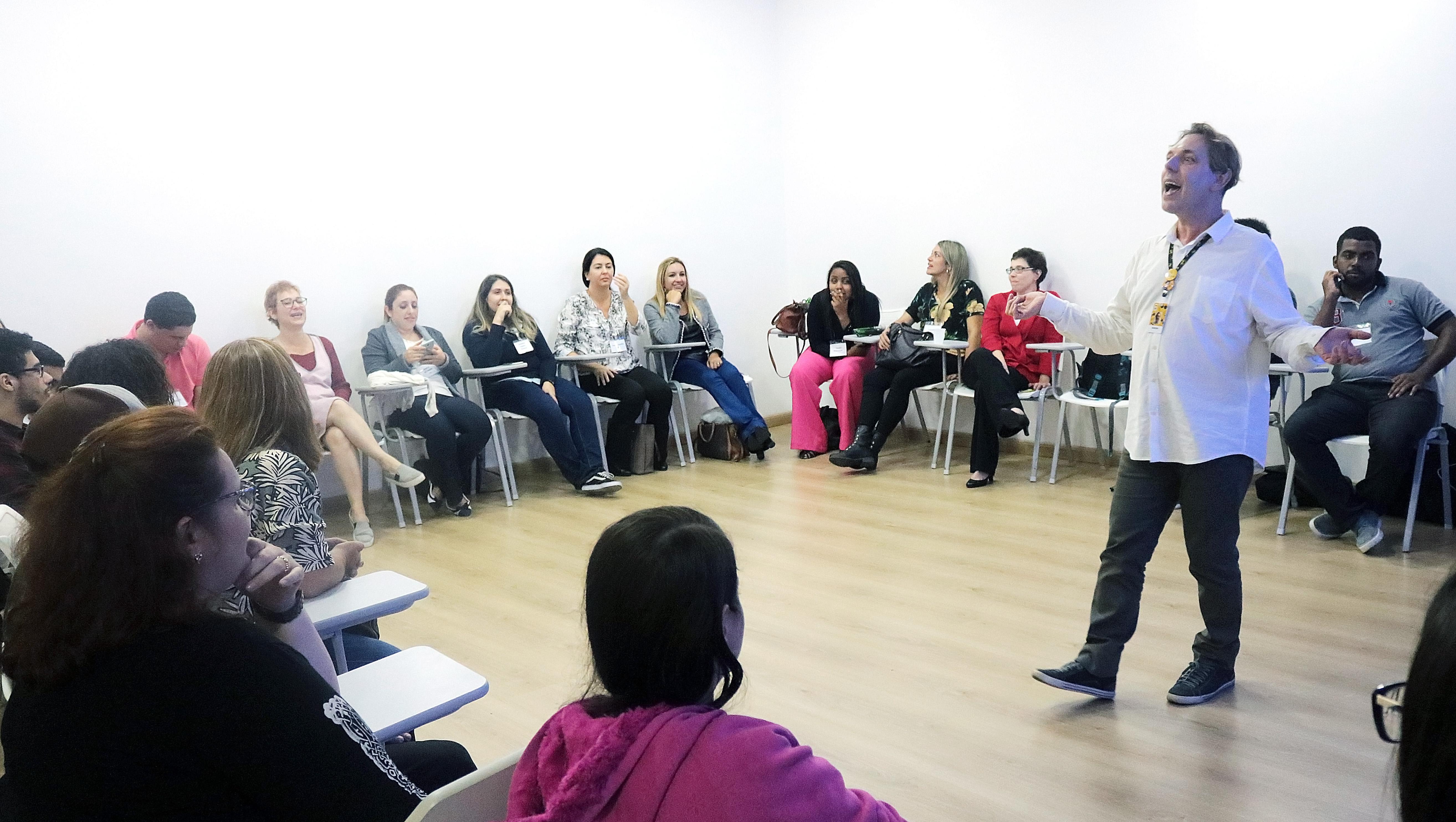 Descrição da imagem: foto de Edson Defendi de pé, ao centro da sala, falando para um grande grupo sentado em roda. Ele está com os braços abertos.