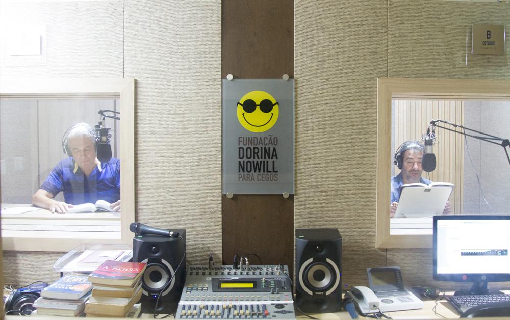Descrição da imagem: foto dos estúdios da Fundação Dorina. Há uma bancada com mesa e caixas de som, telefone, computador e uma pilha de livros. Na parede há duas vidraças por onde é possível ver dois homens com fones de ouvido e microfone, lendo um livro.