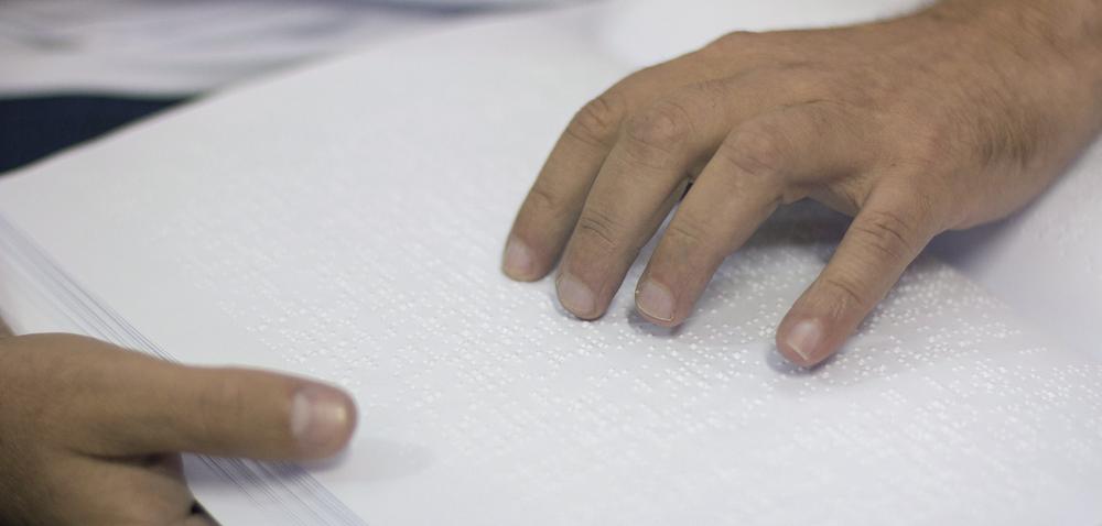 Descrição da imagem: foto de duas mãos tateando uma folha em braille.