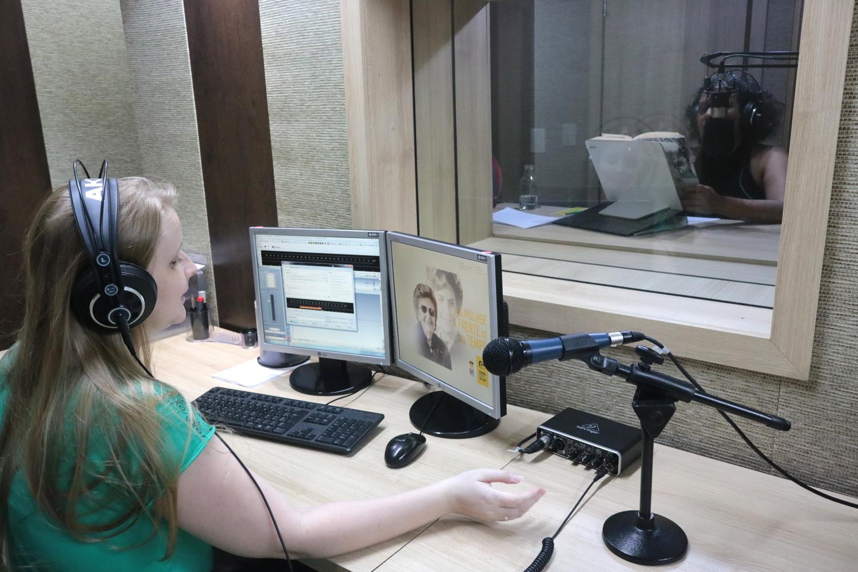 Descrição da imagem: foto de Cláudia Scheer em uma estação de trabalho com dois monitores, teclado, mouse e microfone. Ela está de perfil e usa fones de ouvido. À sua frente, por uma vidraça, é possível ver a ledora Walkiria Brito numa cabine de gravação segurando um livro aberto, com um microfone de estúdio posicionado na altura da cabeça.
