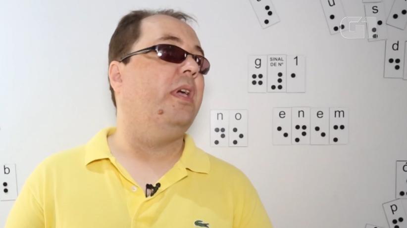 """Descrição da imagem: foto de um homem de óculos escuros retratado do peito pra cima, em meio perfil, com a boca ligeiramente aberta. Ele usa camisa polo amarela e tem um microfone de lapela na gola. Atrás dele há um painel branco com letras em braille que formam a frase """"G1 no Enem"""""""