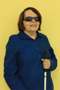 Foto de Regina de Oliveira sobre fundo amarelo. Ela está em pé sorrindo, segurando sua bengala com a mão esquerda à frente do tórax. Ela veste camisa de manga cumprida azul escuro e óculos escuros.