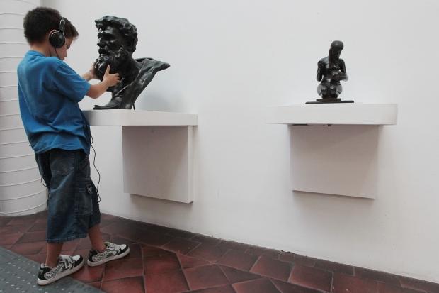 Imagem de um menino na Galeria Tátil da Pinacoteca. Ele está de costas, no canto esquerdo da imagem, usando headfones para ouvir a audiodescrição da obra e tateando o busto de um homem. Ao lado direito está outra escultura. Ambas são pretas e estão sob duas prateleiras brancas, fixadas em uma parede branca. O chão é de lajotas vermelhas e no canto esquerdo aparece a ponta de um piso tátil.