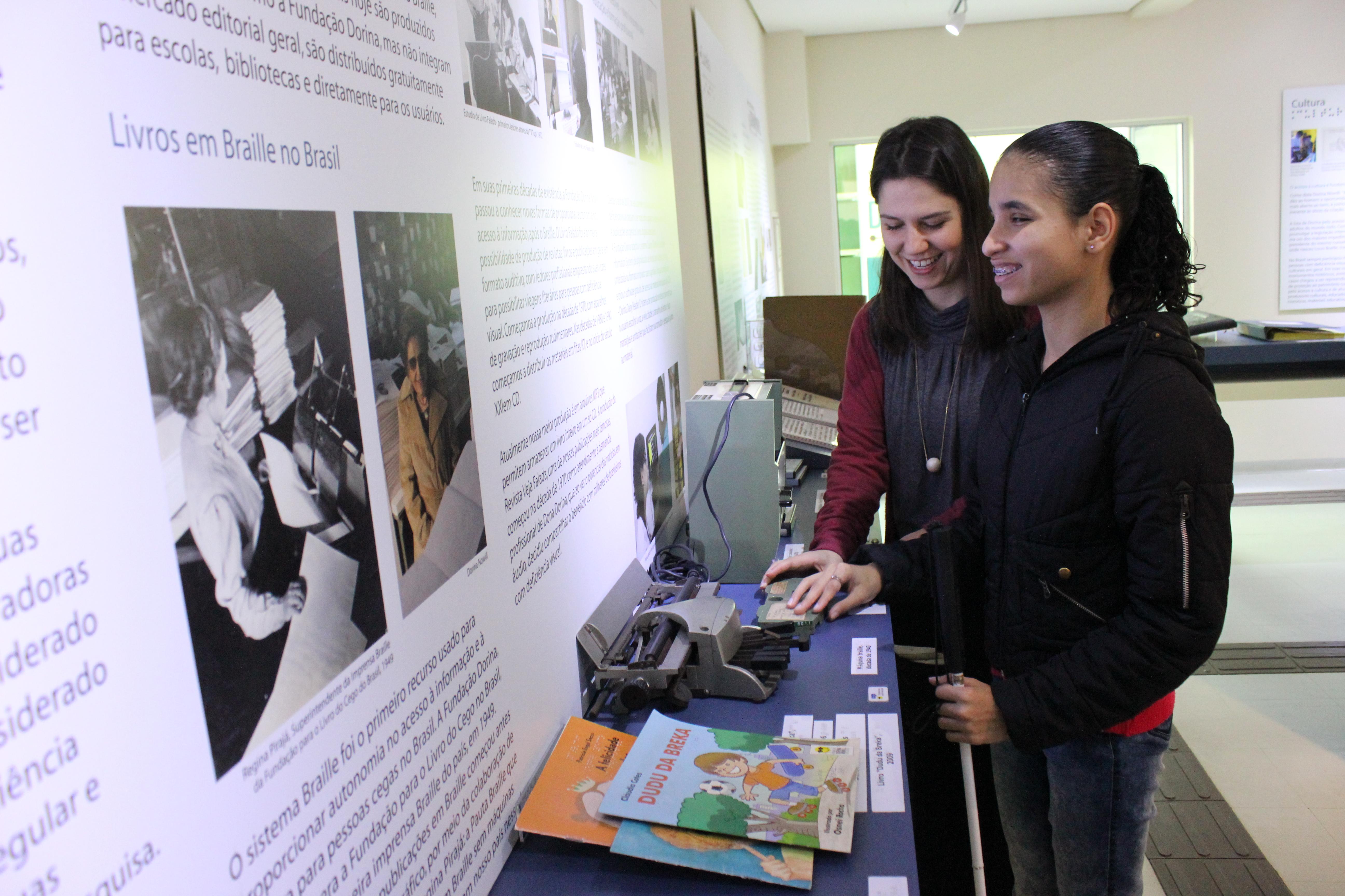 """Imagem de Silvia, educadora do Centro de Memória com uma cliente cega. Elas estão de perfil, sorrindo e tateando um maquinário da exposição que se encontra no Centro de Memória Dorina Nowill. Á frente delas, fixada na parede ao lado esquerdo da imagem, está um painel branco com fotos e textos e a frase em destaque """"Livros em Braille no Brasil"""""""