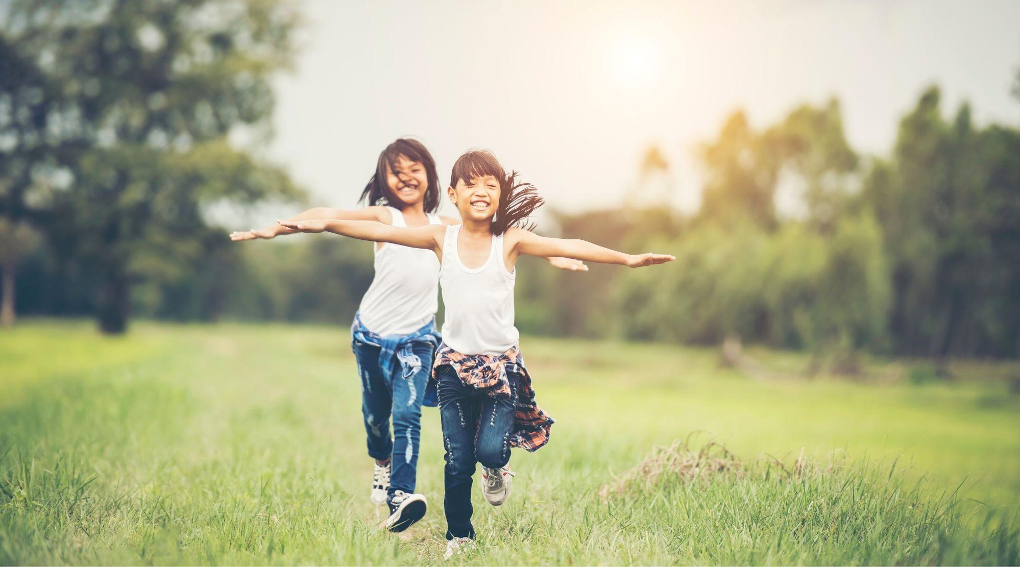 Imagem de duas crianças correndo ao ar livre. Elas estão sorrindo, de braços abertos ao redor de um campo com árvores ao fundo. Ambas as meninas têm traços asiáticos, vestem regata branca, calça jeans e blusa xadrez amarrada na cintura.