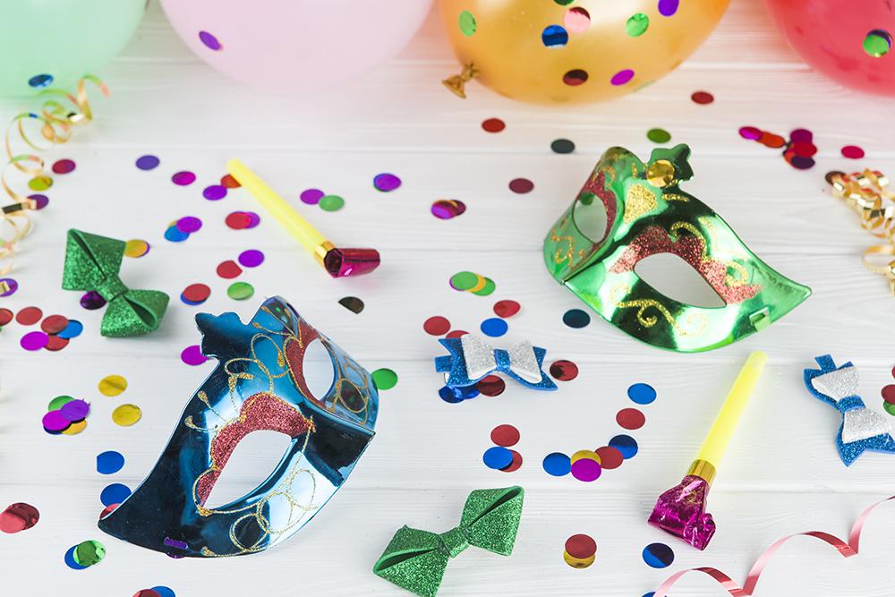 Imagem virtual de confetes e serpentinas coloridos, máscaras de carnaval e bexigas sob uma mesa branca.