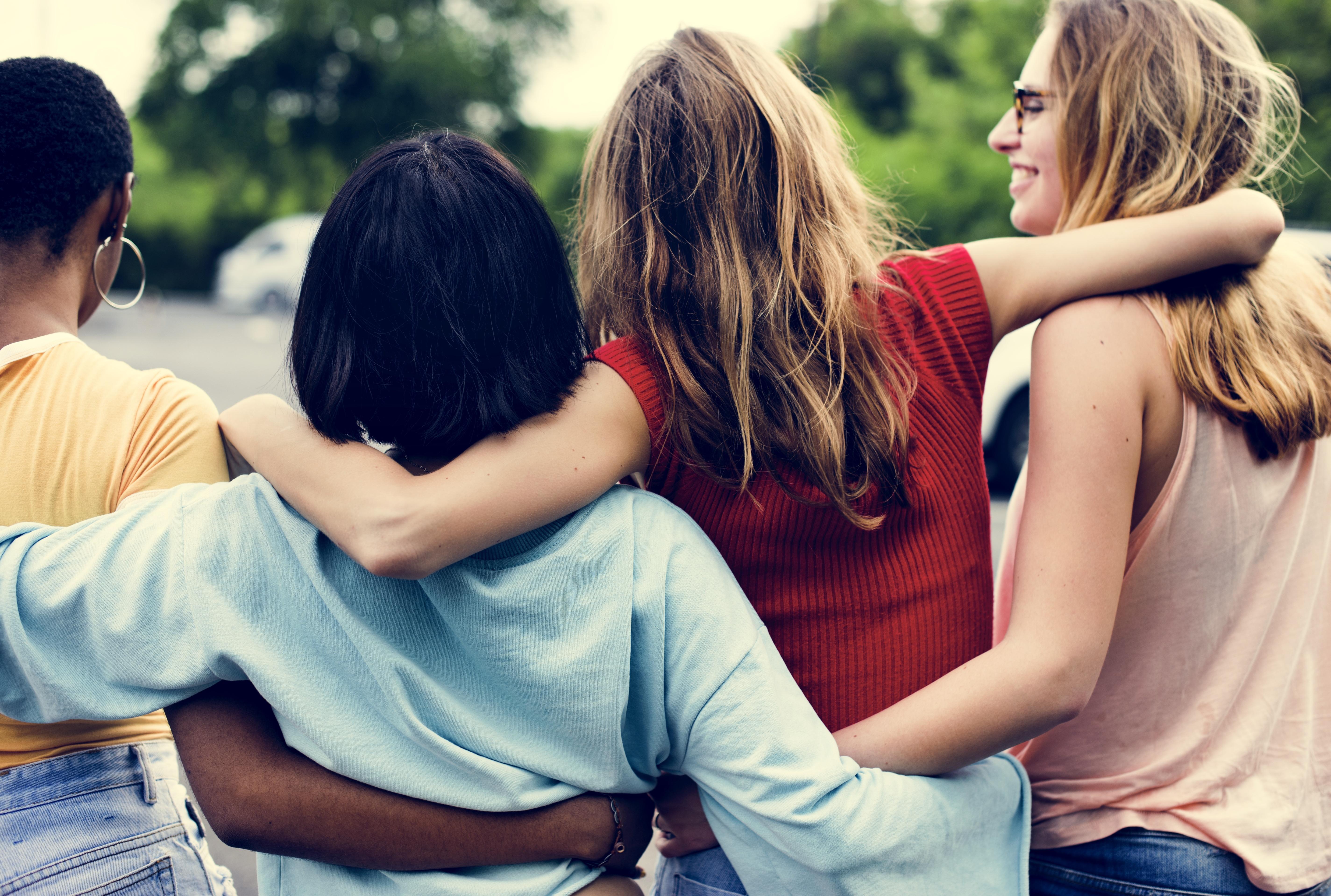 Foto de quatro mulheres andando por um parque. Ao fundo aparecem algumas árvores. Elas estão de costas, perfiladas se abraçando e uma delas está com o rosto de perfil, sorrindo..