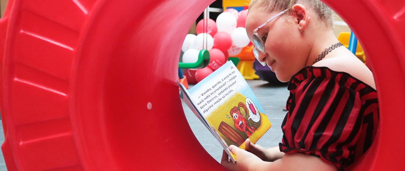 Descrição da imagem: foto de Isabella, uma garota de 9 anos, segurando um livro aberto. Ela usa óculos, está apoiada na parte interna de uma roda de plástico vermelho no mesmo formato de um pneu de trator, olhando para o livro.
