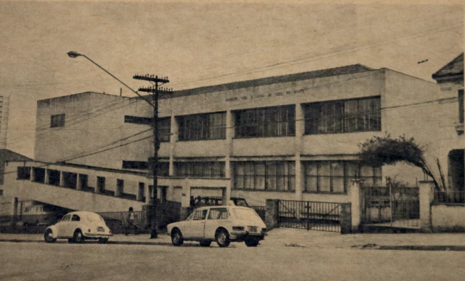 Foto antiga da fachada da então Fundação para o Livro do Cego no Brasil, na década de 1950. Em frente à Fundação estão dois carros estacionados.