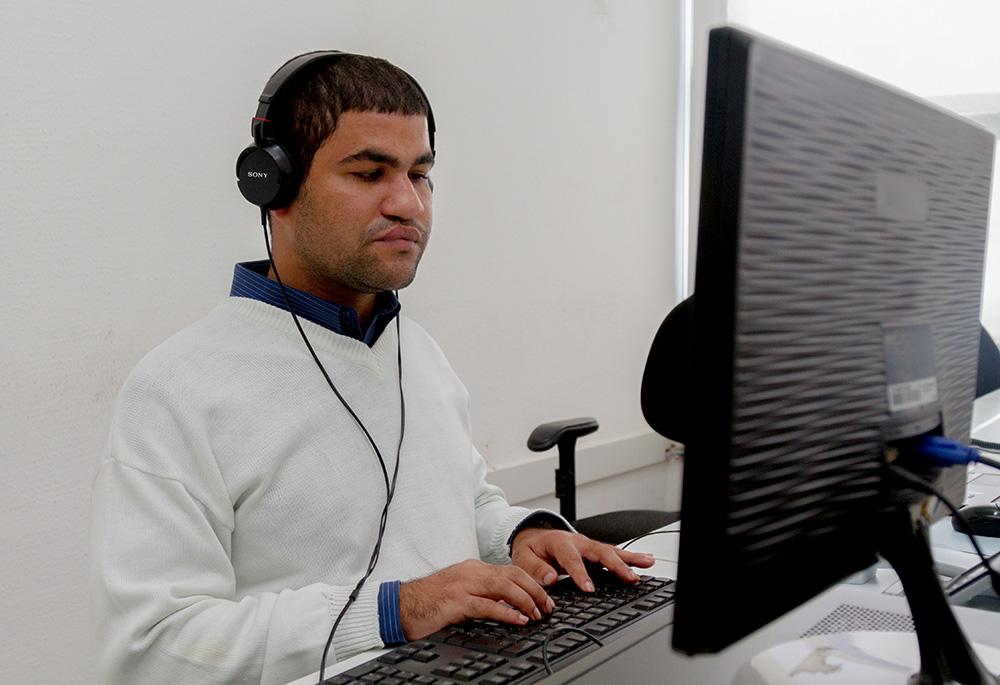 Descrição da imagem: foto de homem à frente de um computador, de olhos fechados, com as mãos sobre o teclado. Ele usa fone de ouvidos na cor preta.