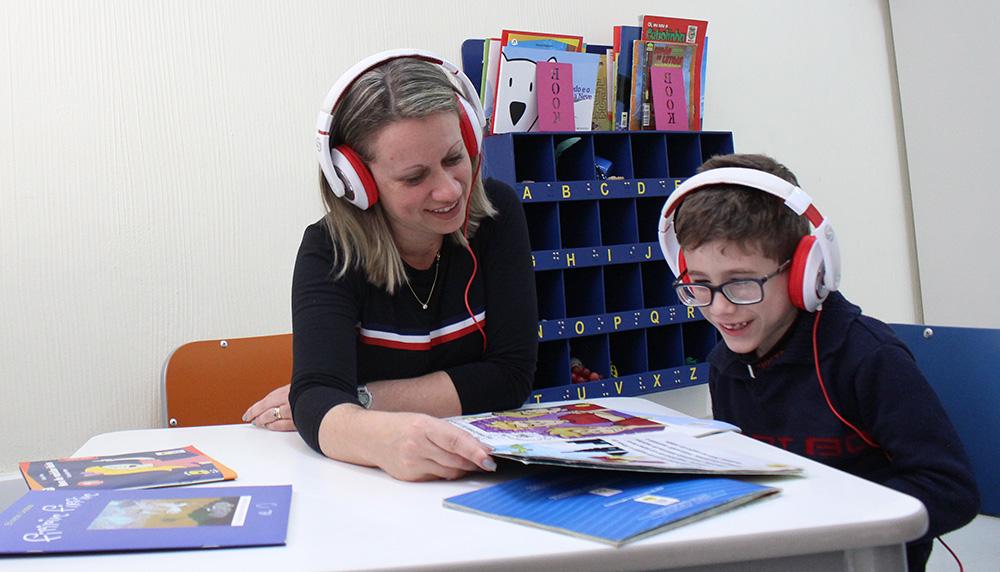 Descrição da imagem: foto de mulher e menino com livros abertos sobre a mesa. Eles usam fones de ouvido. O garoto usa óculos. Eles estão olhando para o livro e sorrindo.