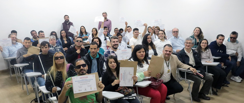 Descrição da imagem: foto de grupo de cerca de 40 pessoas sentadas em cadeiras universitárias. Elas estão sorrindo e muitas exibem seus diplomas para a foto.