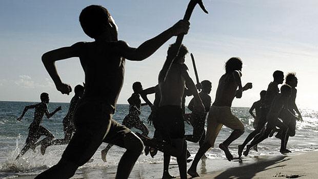 Cena do filme Capitães da Areia. Diversas crianças e adolescentes estão correndo à beira da praia, com alguns objetos nas mãos como pedaços de ferro.