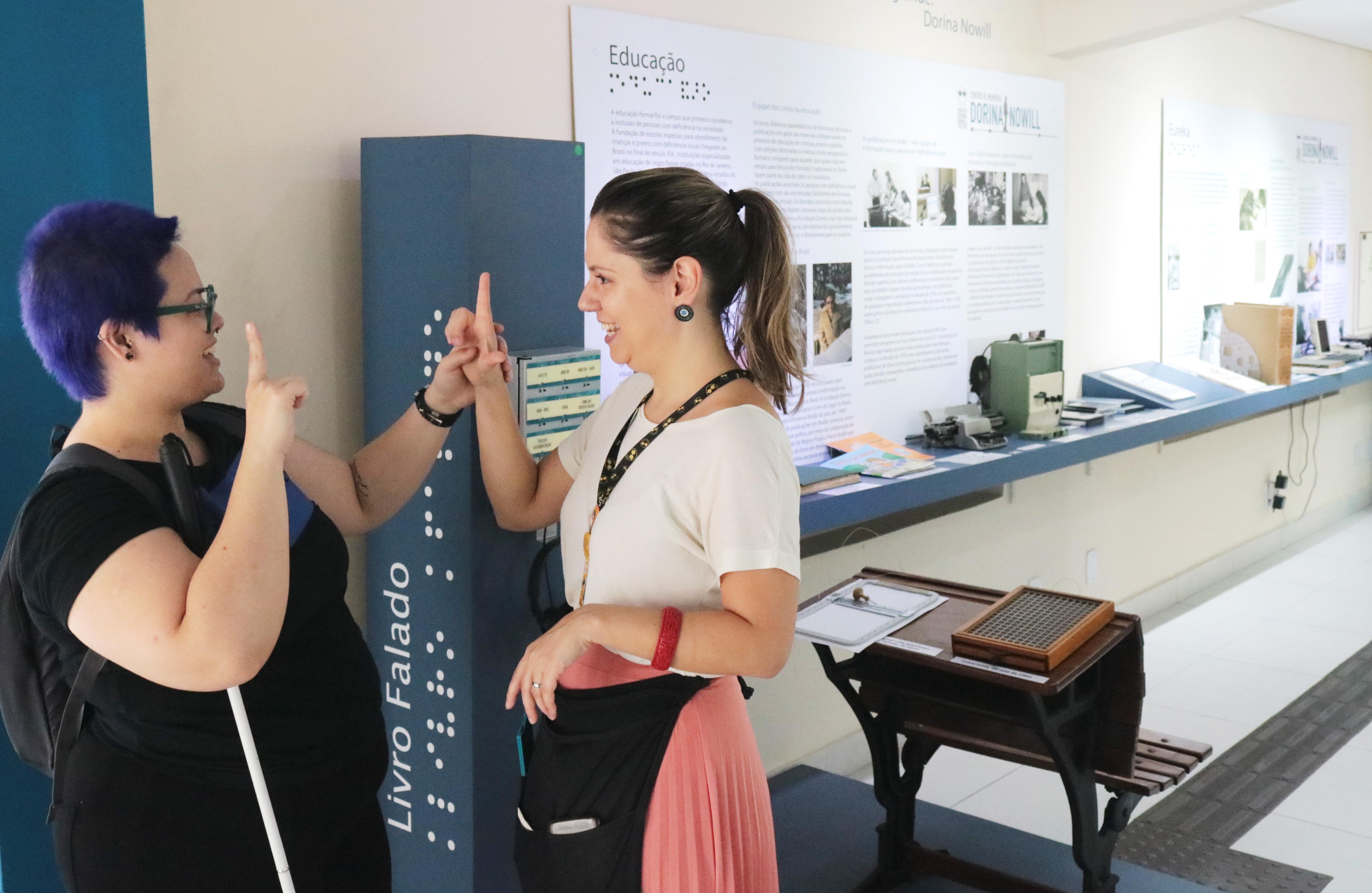 Foto de atendimento no Centro de Memória Dorina Nowill. Silvia, educadora do Centro de Memória, está conversando em libras com uma visitante e, ao fundo, aparecem algumas peças da exposição.