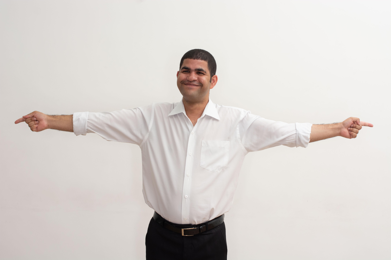 Foto de Ademilson, colaborador da Fundação Dorina. Ele está em pé, sob fundo branco, com os braços abertos para as laterais e sorri. Ele veste camisa branca e calça preta.
