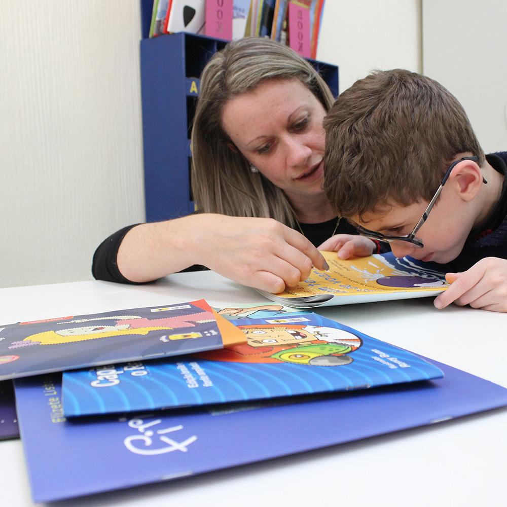 Descrição da imagem: foto de menino e mulher com livro aberto sobre a mesa. O menino usa óculos e está com o rosto bem próximo ao livro.