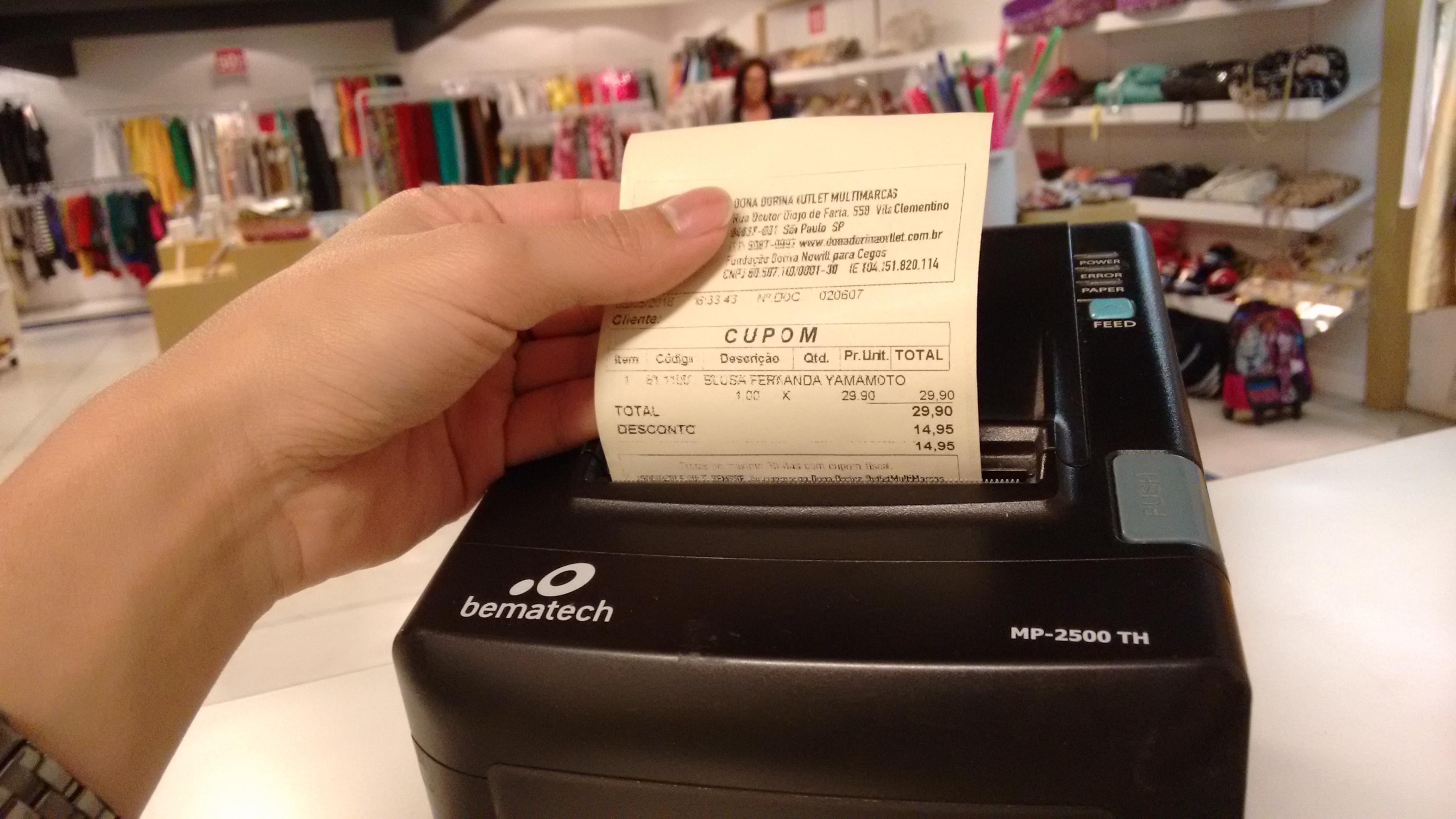 Foto de uma mão segurando um cupom fiscal que está saindo de uma máquina. Ao fundo está o salão do Outlet da Fundação, com diversas peças expostas para venda.