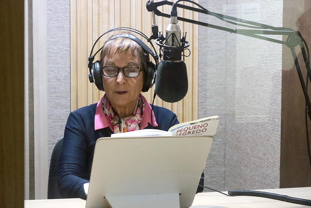 foto de Heloísa Schurmann com um livro aberto sobre prancheta à sua frente. Ela usa fones de ouvido e tem um microfone de estúdio posicionado à altura do rosto.